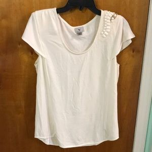 Cream colored top with shoulder embellishment.